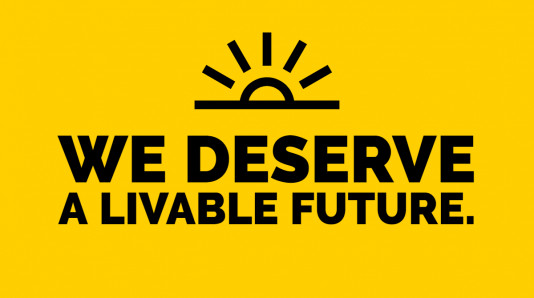 "Black words on a yellow background under a sunrise. ""We deserve a livable future."""